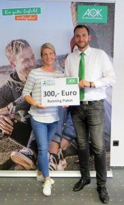 zum Bild: Miriam Budke freute sich über den Hauptpreis, den Sie von Axel Kropp von der AOK Cloppenburg erhielt. Foto: AOK.