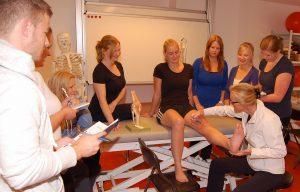 zum Bild: Praktischer Unterricht in der Physiotherapieschule: Der eigene Körper dient als Anschauungsobjekt. Foto: Christliches Krankenhaus Quakenbrück.