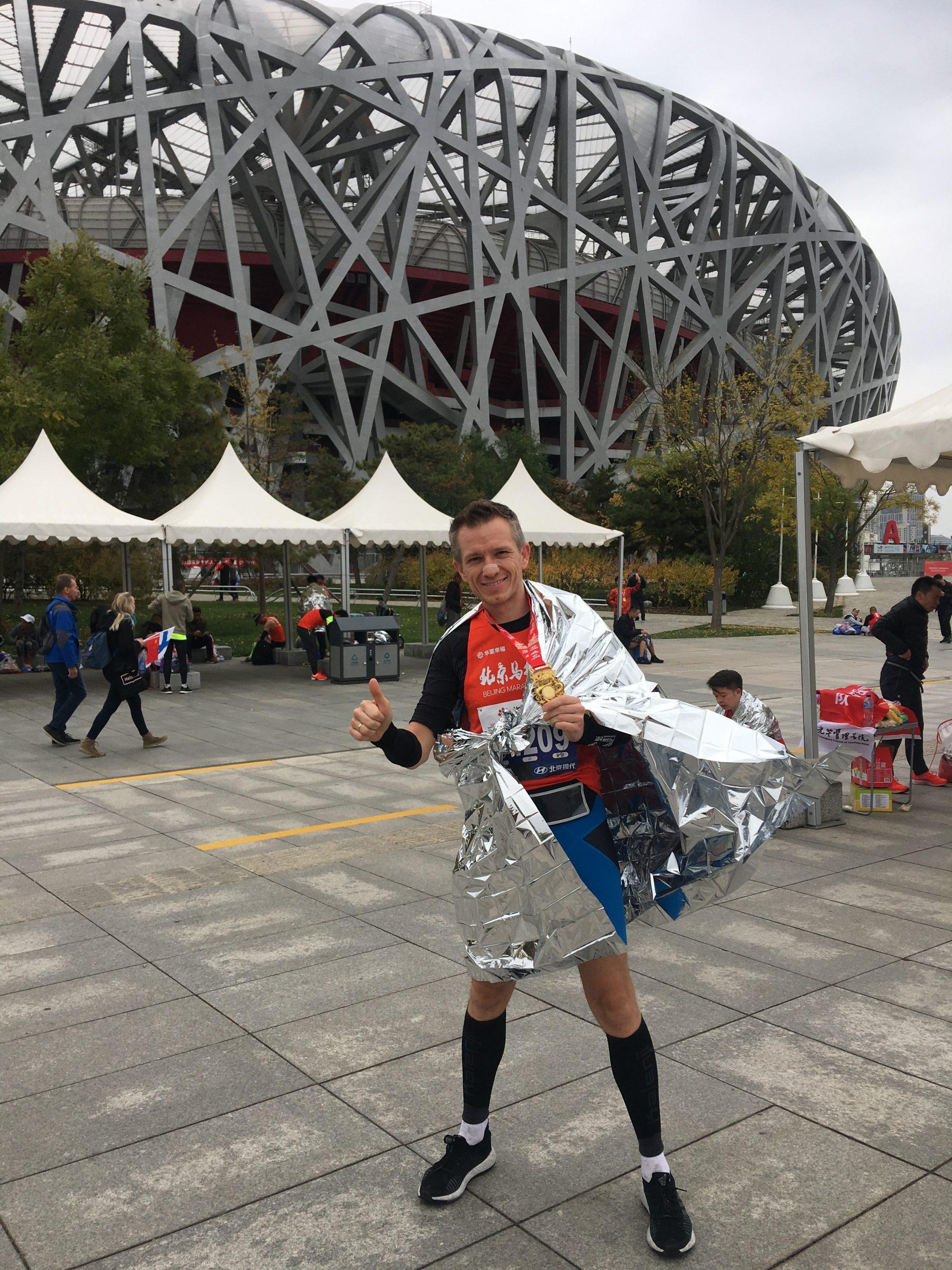 zum Bild: Karl Kicker vor dem Olympiastadion (Vogelnest) in Peking nach dem Peking-Marathon 2019. Foto: Karl Kicker.